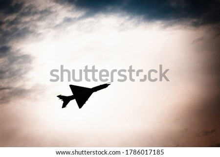 Military aircraft silhouette at dusk, flying at supersonic speed. #1786017185