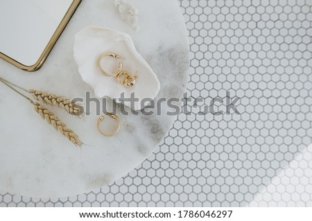 Minimal fashion composition with golden earrings in seashell on marble table with mirror and wheat stalks. Flat lay, top view bijouterie / jewelry concept on mosaic tile background. #1786046297