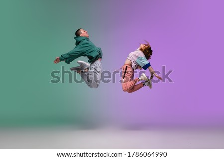 High jump. Boy and girl dancing hip-hop in stylish clothes on colorful gradient background at dance hall in neon. Youth culture, movement, style and fashion, action. Fashionable portrait. Street dance #1786064990