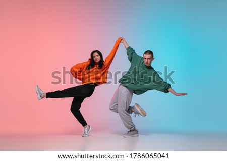 Boy and girl dancing hip-hop in stylish clothes on colorful gradient background at dance hall in neon. Youth culture, movement, style and fashion, action. Fashionable bright portrait. Street dance. #1786065041
