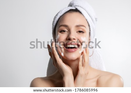 Happy laughing young caucasian woman wrapped in head towel washing face with foam soap cosmetic product. Everyday morning hygiene routine. Skincare and wellness, beauty and cosmetology. Portrait Royalty-Free Stock Photo #1786085996