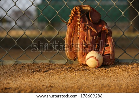 Baseball and Glove against the Field Fence Royalty-Free Stock Photo #178609286