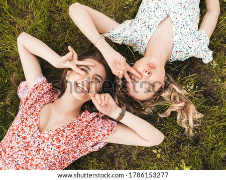 Two young beautiful smiling hipster girls in trendy summer sundress.Sexy carefree women lying on the green grass in sunglasses.Positive models having fun.Top view.They show peace sign #1786153277