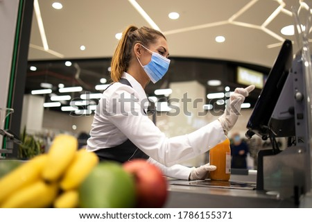People endangered on their workplace because of corona virus. Cashier with protective hygienic mask and gloves working in supermarket and fighting against COVID-19 or corona virus pandemic. Royalty-Free Stock Photo #1786155371