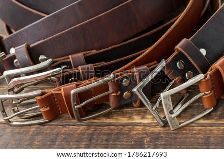 Lots of handmade leather belt on a wooden table. Vintage style brown and cognac leather belts. Leather belts in the style of Heritage with steel buckles. Stylish belts close up. Royalty-Free Stock Photo #1786217693