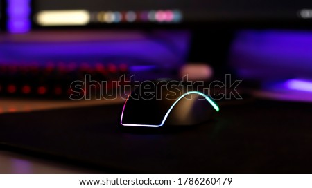 Computer mouse with neon illumination on a white glossy table, dark room, neon light, diodes. Gaming devices, neon lights, white glossy table. Lifestyle, game zone.