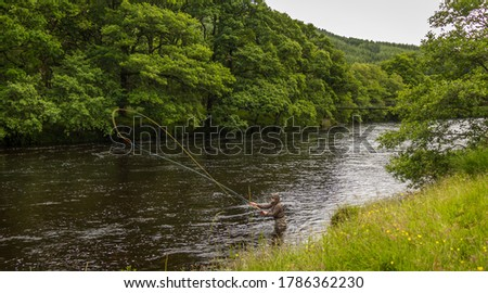 A fisherman spey casting for salmon using a fly rod on the River Orchy, Argyll, Scotland Royalty-Free Stock Photo #1786362230