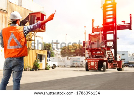 A engineering or foreman or technician give sign and inspect and radio or communication with control center for container stock yard warehouse, forklift logistic transport concept