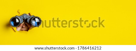 Female hand holds black binoculars on a yellow background. Journey, find and search concept. Banner. Royalty-Free Stock Photo #1786416212