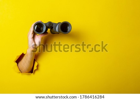 Female hand holds black binoculars on a yellow background. Looking through binoculars, journey, find and search concept