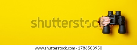 Female hand holds black binoculars on a yellow background. Looking through binoculars, travel, find and search concept. Banner. Royalty-Free Stock Photo #1786503950