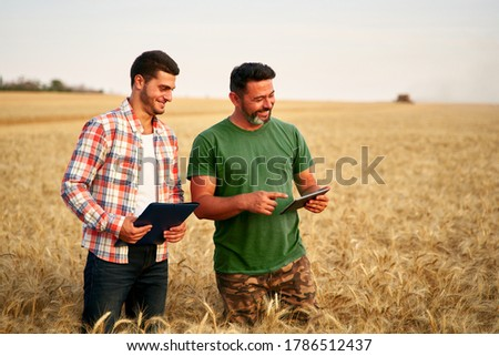 Two farmers stand in wheat stubble field, discuss harvest, crops. Senior agronomist with touch tablet pc teaches young coworker. Innovative tech. Precision farming with online data management soft. #1786512437