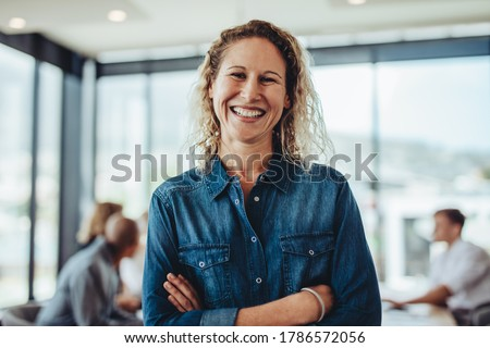 Portrait of smiling businesswoman standing in office with colleagues meeting in background. Successful female professional with her arms crossed. Royalty-Free Stock Photo #1786572056