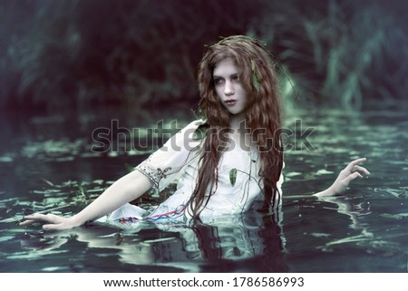 Art photo of a forest drowned woman in the dark muddy water of a swamp
