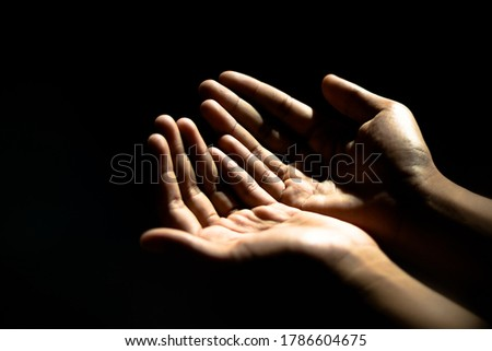 An Asian man is praying for a blessing from God, as the sunlight shines through the palm.  In the empty space at the left to insert text Or use the pictures to compose religious publications
