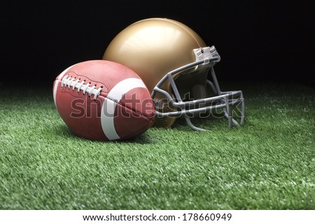 College style football and helmet on grass field against dark background