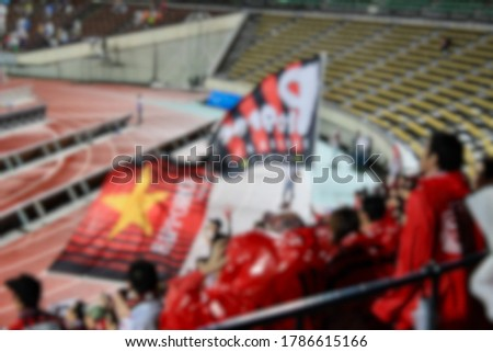 Blur picture of cheering team of away team in black and red uniform with the cheerleader hold megaphone in his hand shouting on a stand in away game at the stadium in Kobe, Japan. Two flags flying.
