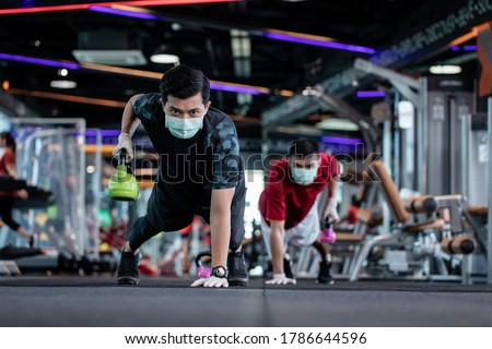 young mam and friend working out wearing surgical mask & latex rubber gloves, COVID-19 pandemic social distancing rules while working out in  a gym, new normal & social distancing concept #1786644596