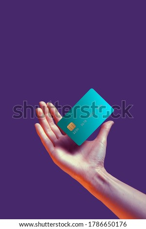 Close up female hand holds levitating template mockup Bank credit card with online service isolated on violet background Royalty-Free Stock Photo #1786650176