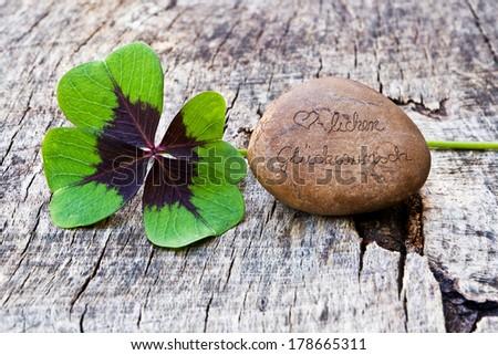 Wood background with four leaf clover and stone, Happy Birthday, Herzlichen Glückwunsch #178665311