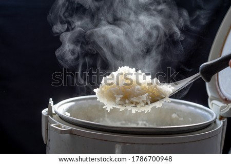 Jasmine rice cooking in electric rice cooker with steam on dark background. Soft Focus, #1786700948