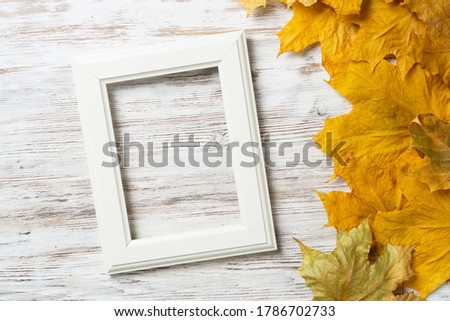Blank rectangular photo frame lies on vintage wooden desk with bright autumn foliage. Flat lay with autumn leaves on white wooden surface. Simple white picture frame with copy space for design.