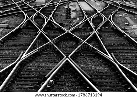 Railway tracks with switches and interchanges at a main line station in Frankfurt Main Germany with geometrical structures, thresholds, gravel and screws. Reflecting symmetrical rails black and white Royalty-Free Stock Photo #1786713194