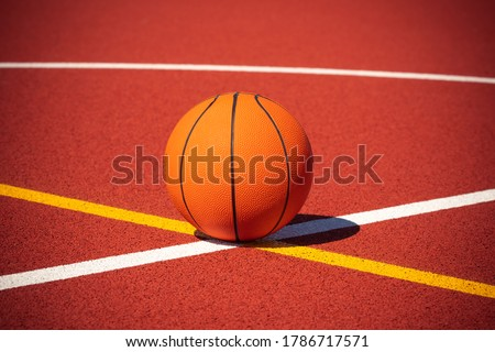 Basketball on the center of outdoor court. Orange ball and court lines on a street court.