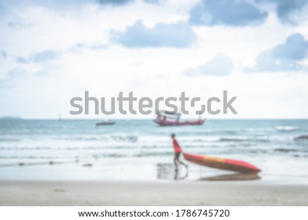 A blurry picture of a man dragging a kayak down the beach With the backdrop of ocean waves, fishing boats and clouds in the sky.