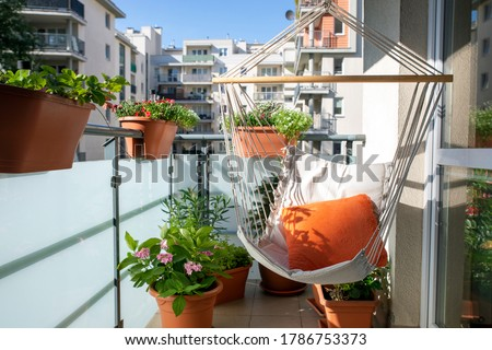 summer balcony with hammock and flowering plants Royalty-Free Stock Photo #1786753373