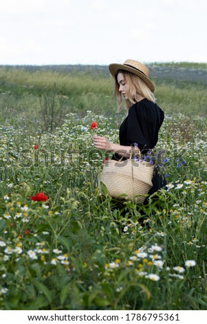 Young adult woman collect flowers on a field in black dress and summer hat with seegrass basket Royalty-Free Stock Photo #1786795361