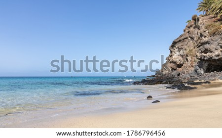 Panoramic photo of the Morrojable beach in Fuerteventura on a sunny day with very calm sea and turquoise water