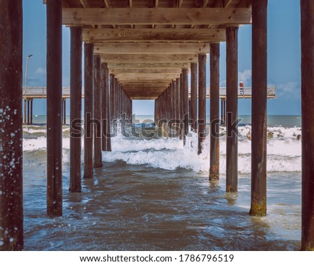 waves under the wooden pier on a clear day  Royalty-Free Stock Photo #1786796519