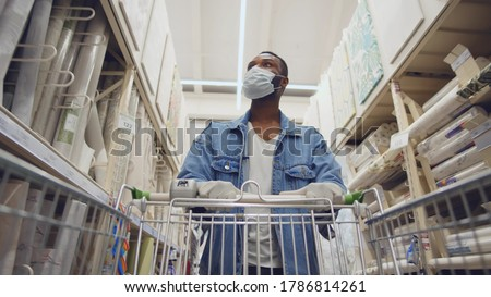 African man wearing protection facemask choosing wallpaper in hardware store. Low angle view of afro guy pushing shopping cart buying materials in house improvement store wear safety mask and gloves Royalty-Free Stock Photo #1786814261