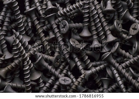 Black steel self-tapping screws used in handicrafts background texture Royalty-Free Stock Photo #1786816955