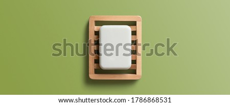 White bar of soap in wooden dish on a green background. Top view, flat lay. Royalty-Free Stock Photo #1786868531
