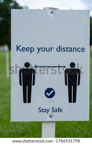 A close up of a sign asking people to socially distance and stay safe at an outdoor event as the coronavirus lockdown eases in England