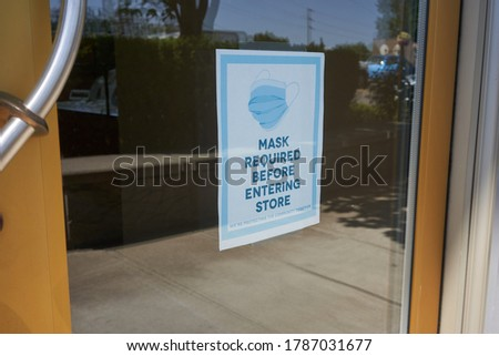 Mandatory mask policy signage at the entrance to a retail store during the coronavirus pandemic.