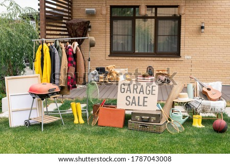 Garage sale in backyard: various toys, household stuff and clothes putting on sale Royalty-Free Stock Photo #1787043008