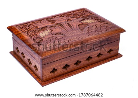 Wooden closed carved casket handmade. Patterns of Indian culture in the form of Golden elephants and wood. Isolated on a white background
