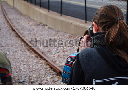 Posterior side-angle view of a women wearing black jacket taking picture with a camera in focus and out of focus railway track in background.