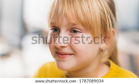Portrait of a Cute Little Girl with Blond Hair Sitting at her School Desk, Smiles Happily. Smart Little Girl with Charming Smile Sitting in the Classroom. Close-up Portrait Shot