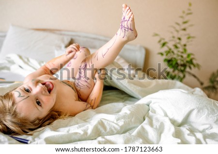 Cute baby draws with a marker on a white bed. smeared hands and feet, dirty in paint. Funny picture, funny kid.