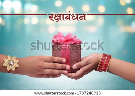 raksha bandhan (rakhi, rakshabandhan) concept, Indian brother giving gift to his sister, Raksha Bandhan Hindi calligraphy and Marathi calligraphy which reads as ' Raksha bandhan