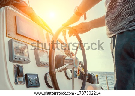 Hand of man on the steering wheel sailboat. Hands on the sailboat's steering wheel. Man's Hands with clocks Steering Wheel Of Yacht. Close-up of a man's hands on the yacht steering wheel. Helm yacht #1787302214
