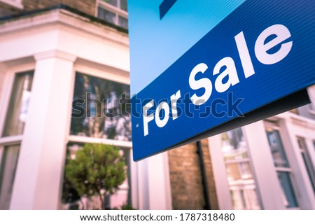 Estate agent For Sale sign on street of houses Royalty-Free Stock Photo #1787318480