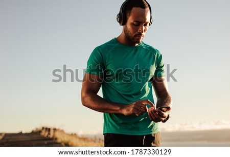 Portrait of an athlete using mobile phone during morning run. Athletic man listening to music on wireless headphones. Royalty-Free Stock Photo #1787330129
