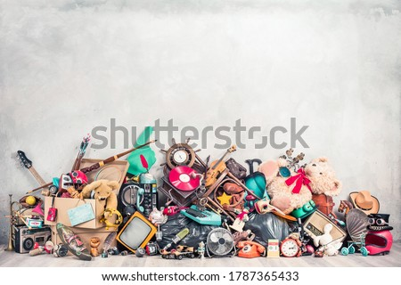 Old antiques and retro collectibles memorabilia dumped in a huge pile. Garage sale, attic room storage conceptual still life or disposal and recycling of outdated objects. Vintage style filtered photo Royalty-Free Stock Photo #1787365433