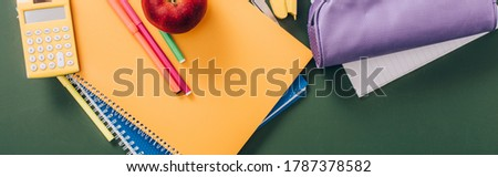 top view of multicolored notebooks and school supplies on green chalkboard, horizontal image
