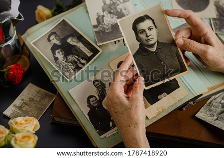 Female hands holding and old photo of her mother. Vintage photo album with photos. Family and life values concept.